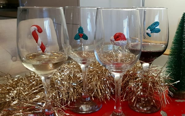 Wine glasses turned into handmade Christmas goblets with candy cane, holly and a Santa Claus hat made from coloured epoxy putty which would make a great gift